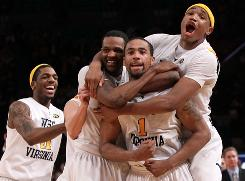 Da'Sean Butler (1) celebrates with teammates John Flowers, left, Devin Ebanks, center, and Kevin Jones, right, after making a game-winning shot to beat Cincinnati in the Big East tournament. Behind Butler, the Mountaineers hope to pull off four more wins to bring a national championship back to Morgantown, W.Va.
