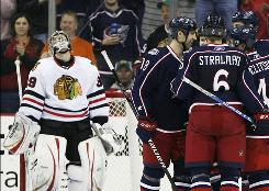 Blue Jackets players celebrate a third-period goal while Blackhawks goalie Cristobal Huet looks up as Chicago fell hard on the road.