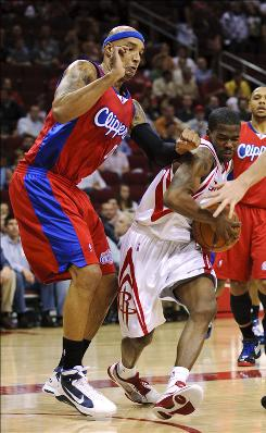 The Rockets' Aaron Brooks drives through the Los Angeles Clippers' Drew Gooden during the first quarter Thursday night in Houston. Brooks scored 18 points, tying Trevor Ariza for Houston's leading scorer.