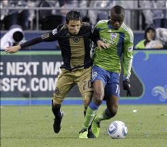 The Sounders' Steve Zakuani, right, battles the Union's Roger Torres during the opening game of the 2010 MLS season.