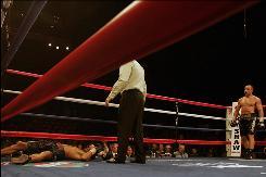 Arthur Abraham, right, watches as the referee attends to Andre Dirrell during the 11th round of their Super Six fight. Abraham was disqualified after landing an illegal punch.