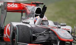 McLaren driver Jenson Button waves to the crowd after prevailing in the Australian Grand Prix for his first win of the season.