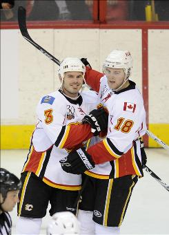 The Flames' Ian White (3) celebrates his goal with Matt Stajan as Calgary bested the Capitals to move within four points of the eighth-place spot in the Western Conference standings.