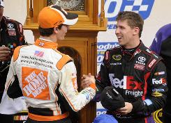 Denny Hamlin, right, shakes hands with teammate and runner-up Joey Logano in victory lane at Martinsville Speedway in front of the track's traditional grandfather clock trophy.