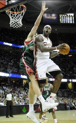 LeBron James drives against Bucks center Andrew Bogut during their game Wednesday night in Cleveland. James had 23 points as the Cavaliers slipped past Milwaukee 101-98.
