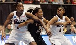 Connecticut's Tina Charles, left, and Tiffany Hayes put the squeeze on Florida State's Chasity Clayton during a free throw in the Dayton regional final.