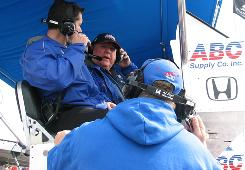 A.J. Foyt (center) and team engineer Jeff Britton talk strategy from atop the pit box as Larry Foyt listens in.