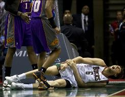 Bucks center Andrew Bogut yells in pain after falling to the court with an elbow injury during the second quarter against the Suns. Despite his absence, Milwaukee won to end Phoenix's 10-game winning streak.