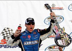Kevin Harvick grabs a coke and raises the winner's guitar in victory lane after taking Saturday's NASCAR Nationwide Series Nashville 300.