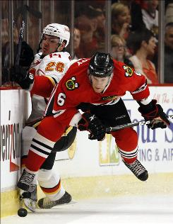 Chicago's Jordan Hendry, right, battles for the puck with Calgary's Ales Kotalik during the first period.