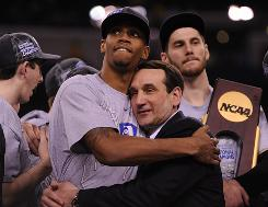 Duke coach Mike Krzyzewski hugs senior forward Lance Thomas after the Blue Devils beat Butler for the school's fourth national championship.