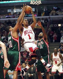 The Bulls' Derrick Rose attempts to drive past the Bucks' Kurt Thomas, left, and John Salmons in the first quarter Tuesday night in Chicago. Rose scored 12 points.