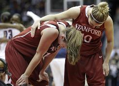 Stanford's JJ Hones, right, comforts Kayla Pedersen after UConn put the finishing touches on its NCAA championship victory in San Antonio. Stanford held a 20-12 lead at halftime but couldn't keep up with the Huskies in the second half.
