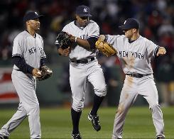 From left, New York Yankees outfielders Randy Winn, Curtis Granderson, and Marcus Thames celebrate on the field after their 6-4 victory over the Boston Red Sox.
