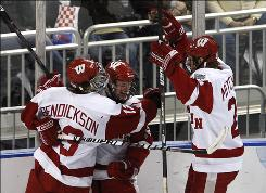 Wisconsin center Aaron Bendickson, left, and wingers Jordy Murray, center, and John Mitchell celebrate a second-period goal as the Badgers advanced to Saturday's Frozen Four title game.