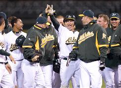Oakland second baseman Mark Ellis, center, is congratulated by teammates after driving in the game-winning run against Seattle during the 10th inning.