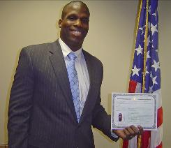 Former University of Evansville basketball player Kwame James shows off his certificate of citizenship after becoming a naturalized American earlier this week.