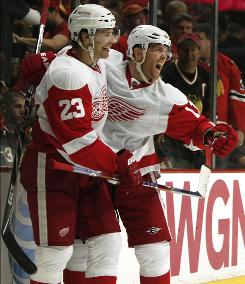 Brad Stuart, left, celebrates his game-winning overtime goal with Red Wings teammate Dan Cleary after ending the Blackhawks' chances of clinching the No. 1 seed in the Western Conference.