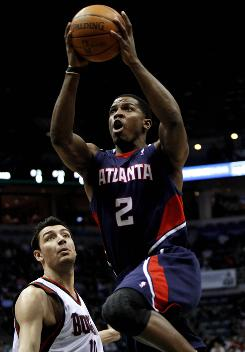 The Atlanta Hawks' Joe Johnson goes up for a shot against the Milwaukee Bucks' Carlos Delfino in the first half. Johnson scored 31 points.