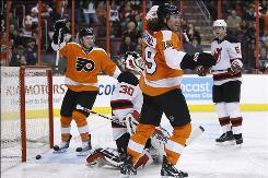 The Flyers' Scott Hartnell, center, and Claude Giroux, left, celebrate a goal by teammate Kimmo Timonen as Devils goalie Martin Brodeur and Colin White look on in the second period of the two teams' last regular-season matchup on March 28. Philadelphia won 5-1.