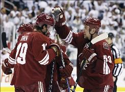 The Coyotes' Derek Morris, right, celebrates a goal against the Detroit Red Wings by teammate Wojtek Wolski with Shane Doan, left, in the second period Wednesday night. Wolski scored on an assist from Morris, who also scored one of his own.