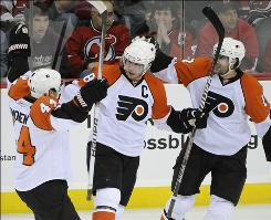 The Flyers' Mike Richards, center, celebrates his goal with teammates Kimmo Timonen, left, and Simon Gagne during the second period of first-round playoff action against the Devils. Richards scored seven minutes after Chris Pronger scored the first goal of the game on a power play.