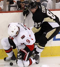 Pittsburgh Penguins center Sidney Crosby collides with the Ottawa Senators' Milan Michalek during the second period of Wednesday's game.