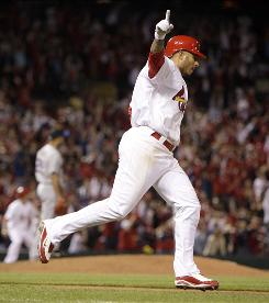 The Cardinals' Felipe Lopez celebrates as he rounds the bases after hitting a grand slam off New York Mets pitcher Raul Valdes during the seventh inning.