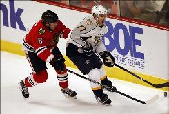 The Predators' J.P. Dumont (71), carrying the puck away from the Blackhawks' Jordan Hendry during the first period, scored twice as Nashville earned its first road playoff victory.