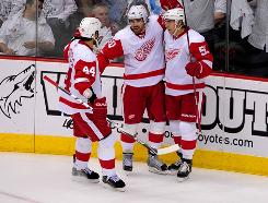 Henrik Zetterberg, center, being congratulated by Red Wings teammates after a second-period goal, notched a hat trick as Detroit evened its series with Phoenix at 1-1.