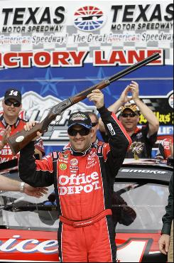 Tony Stewart holds the pole award, a Turnbull Model 1886 Take-Down Rifle, after qualifying first for Sunday's Samsung Mobile 500.