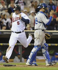 Twins right fielder Michael Cuddyer scores behind Kansas City Royals catcher Jason Kendall on a single by J.J. Hardy during the eighth inning. Cuddyer had two hits and three RBI.