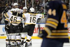 The Boston Bruins swarm defenseman Zdeno Chara after his third-period goal against Buffalo.