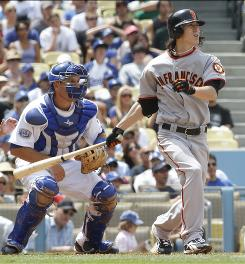 Giants starting pitcher Tim Lincecum hits a two-run single as Los Angeles Dodgers catcher A.J. Ellis watches during the third inning. Lincecum had three hits and three RBI while shutting out the Dodgers in six innings of work.