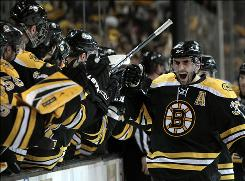 Patrice Bergeron high-fives the Bruins bench after scoring the decisive third-period goal that lifted Boston to a Game 3 win over the Sabres.