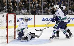 Kings center Anze Kopitar scores past Canucks goalie Roberto Luongo as defenseman Kevin Bieksa looks on during the second period in Game 4 in Los Angeles Wednesday night.