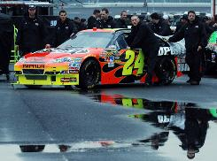 Jeff Gordon's crew pushes his car through the garage on a rainy Saturday morning at Talladega Superspeedway.