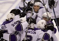 The Los Angeles Kings celebrate Anze Kopitar's Game 2 overtime goal, scored on a power play after the Vancouver Canucks were called for too many men on the ice.