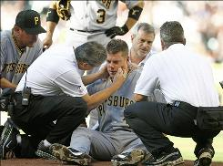 Pittsburgh trainers examine starter Chris Jakubauskas after he was hit in the face with a line drive off the bat of the Astros' Lance Berkman in the first inning.