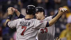 The Twins' Justin Morneau (33) celebrates with teammate Joe Mauer after hitting a two-run, game-tying home run in the seventh inning.