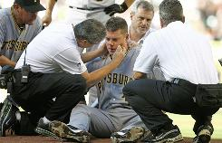 Pirates pitcher Chris Jakubauskas is treated by team trainers after being hit in the head with a line drive off the bat of Houston's Lance Berkman during their game Saturday.