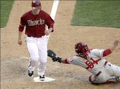 The Diamondbacks' Mark Reynolds steps on home plate before Phillies catcher Carlos Ruiz can apply the tag during the eighth inning. Reynolds' RBI double in the eighth broke a 6-6 tie.