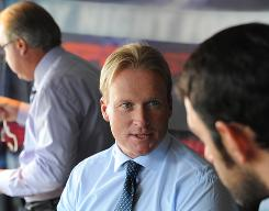 Monday Night Football analyst Jon Gruden prepares for a game last summer with spotter Tony Granieri, forefront, and Ron Jaworski.