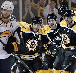 Buffalo Sabres winger Jason Pominville, left, skates away as, from left, the Bruins' Mark Recchi, Matt Hunwick, David Krejci, and Zdeno Chara celebrate Recchi's first-period goal. Krejci netted twice and made an assist as Boston clinched its first playoff series at home since 1999.