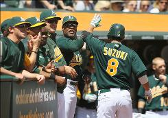 The Athletics congratulate Kurt Suzuki after hitting a three-run home run in the first inning against the Yankees on April 22. The A's won 4-2.