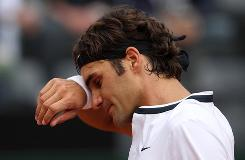 Roger Federer of Switzerland wipes his brow during his loss Tuesday to Ernests Gulbis of Latvia during the Rome Masters.