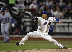 Mets relief pitcher Hisanori Takahashi winds up in the fourth inning as the Dodgers' A.J. Ellis leads off third base in the second game of Tuesday's doubleheader in New York.