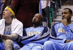 Denver Nuggets players, Chris Andersen, left, Anthony Carter, center, and Malik Allen watch the final seconds of Game 4 in the first round, a 117-106 loss to the Jazz.