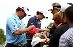 Lee Westwood of England, left, and Rory McIlroy of Northern Ireland sign autographs for spectators Tuesday during a practice round for the Quail Hollow Championship in Charlotte.