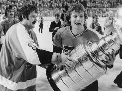 Goaltender Bernie Parent, left, and forward Bobby Clarke carry the Stanley Cup after the Flyers won their second straight NHL title in 1975.